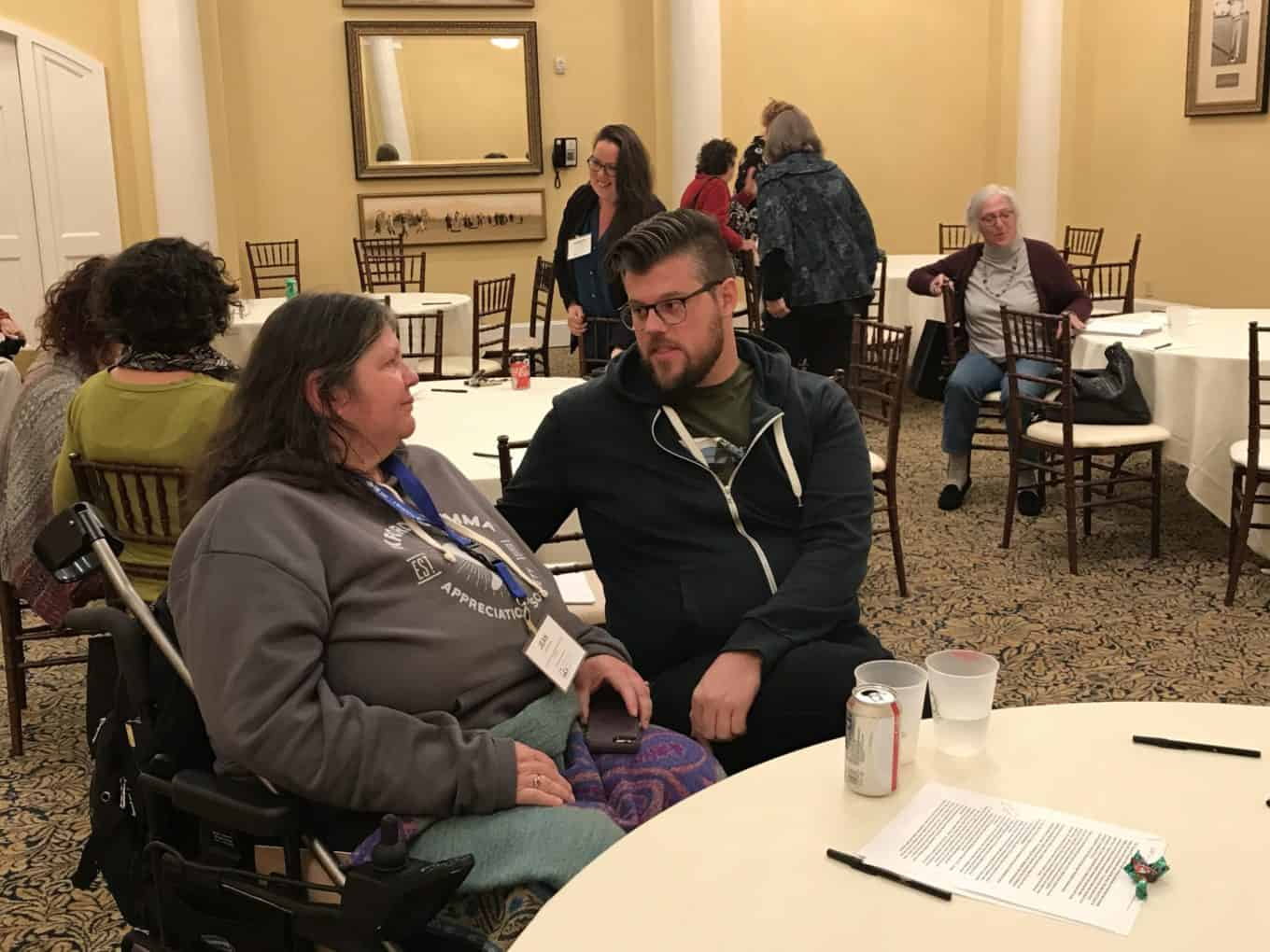 A man talks to a woman sitting in a wheelchair, they're talking about Medicaid transformation