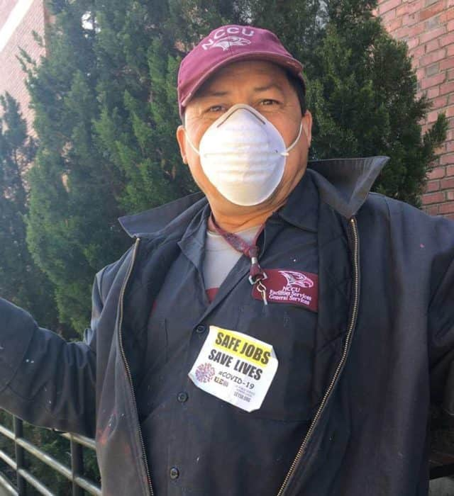 service industry worker poses outside with a mask on.
